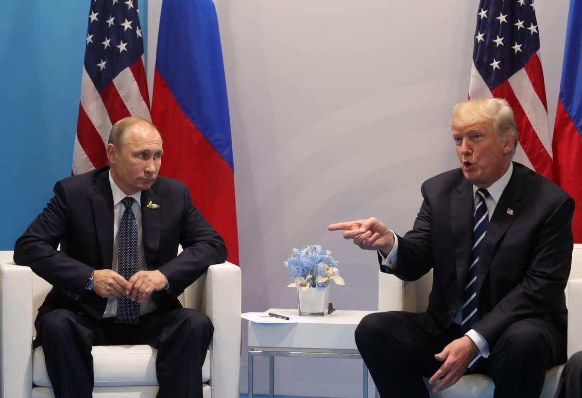 Vladimir Putin ja Donald Trump istuvat keskustelemassa valkoisilla sohvilla.