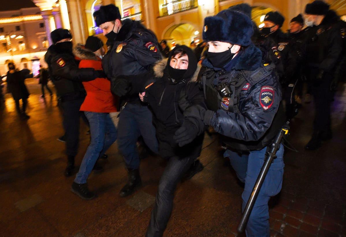 Poliisit raahaavat mielenosoittajaa Pietarissa.