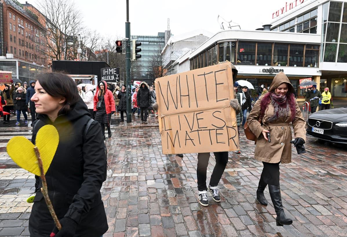 White lives matter -pahvikylttiä kantava mielenosoittaja.