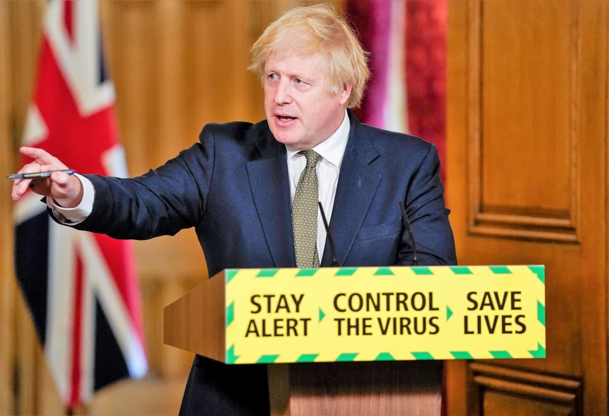Boris Johnson pitää tiedotustilaisuutta tummanisinisessä puvussa, harmaassa kravatissa . Johnson viittoo oikealla kädellään. Hän seisoo  puhujanpöntön takana. Pöntössä tekstit: Stay alert. Control the virus. Save lives.