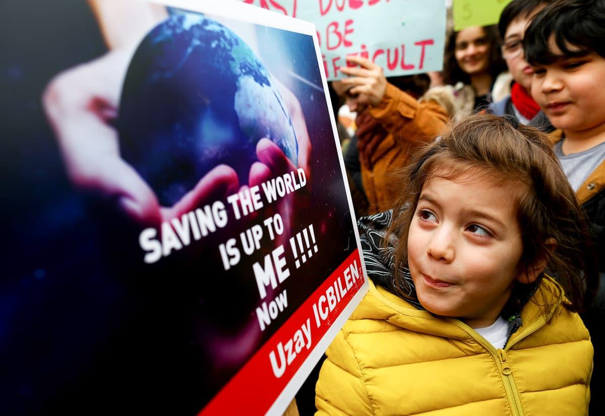 """Nuori tyttö, jolla lukee kyltissä """"Saving planet is up to me now!"""""""