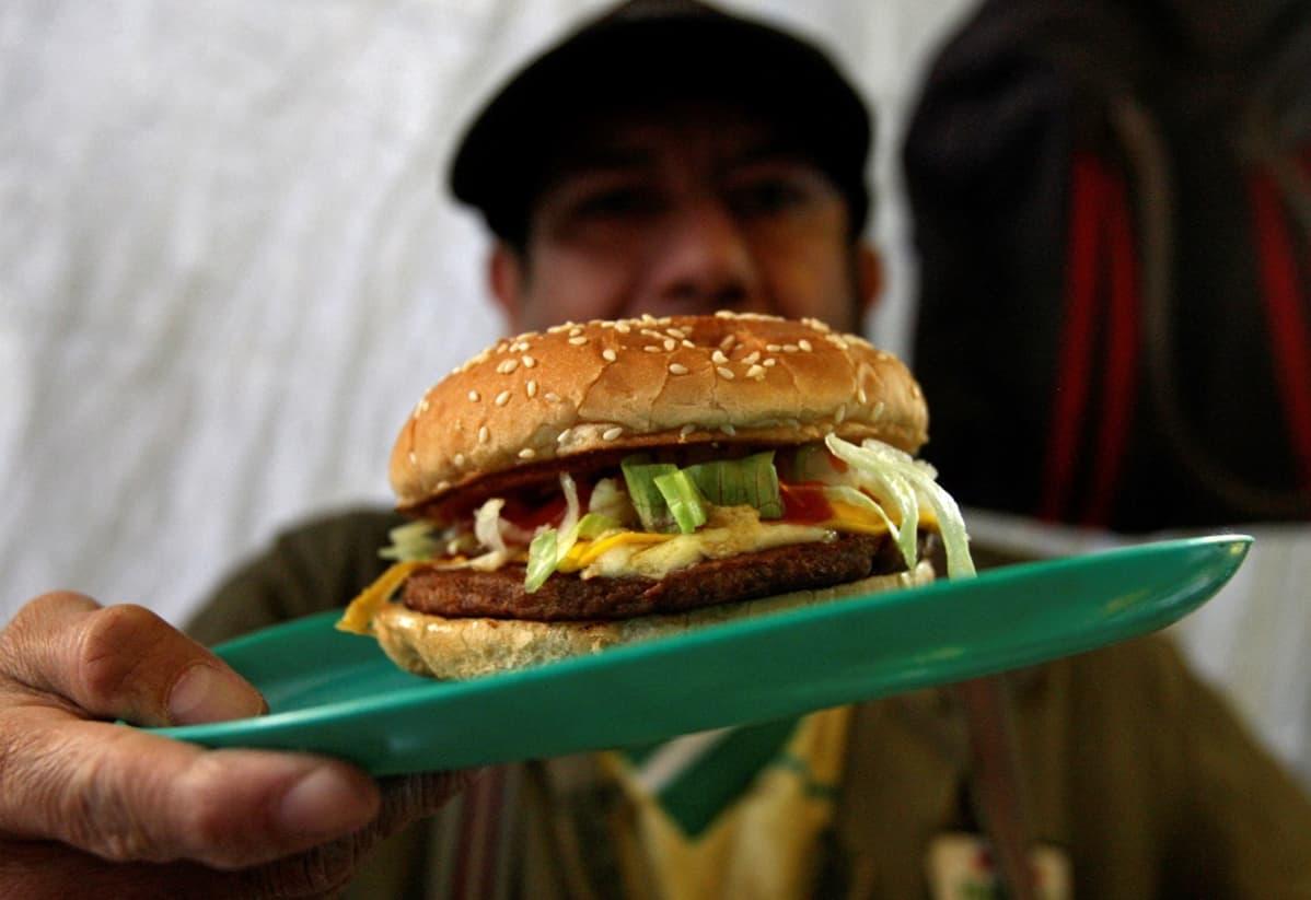 Kuvassa mies pitää edessään lautasta, jolla on hampurilainen.