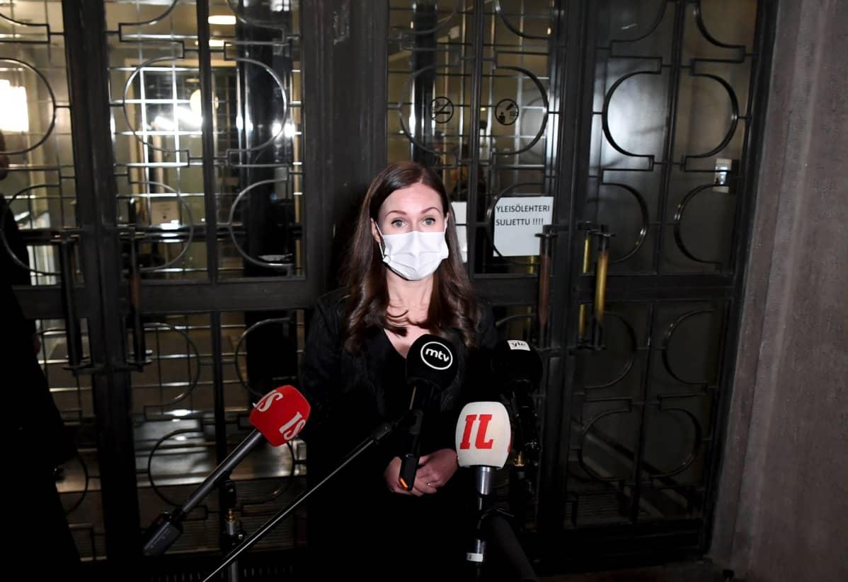 Statsminister Sanna Marin (SDP) svarar på journalisters frågor utanför riksdagen den 21 december 2020.