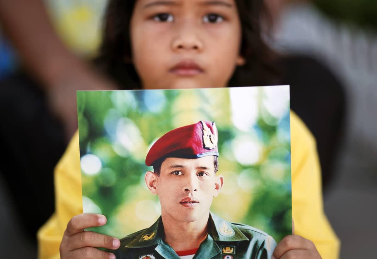 Thaityttö kunnioitti uutta kuningasta palatsin ulkopuolella Bangkokissa lauantaina.