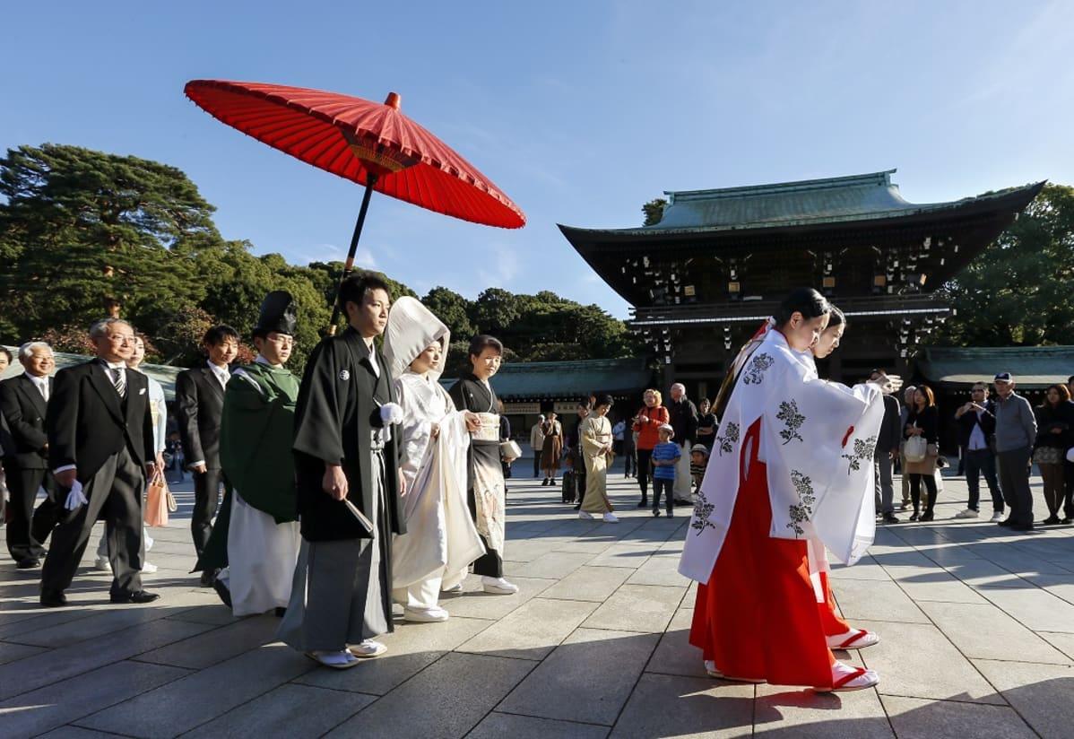 Kimonoihin pukeutunut hääpari seuraa kahta juhla-asuista nuorta naista, ihmisiä kävelee heidän perässään. Sivustakatsojia on pysähtynyt seuraamaan kulkuetta.