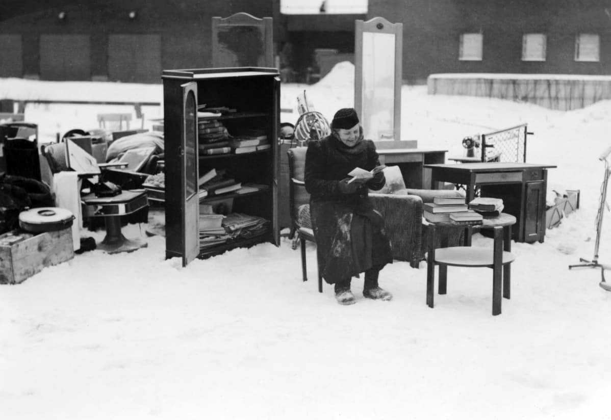 Nainen istuu ulkona talvella tuolilla ja lukee kirjaa, taustalla talon irtaimistoa.