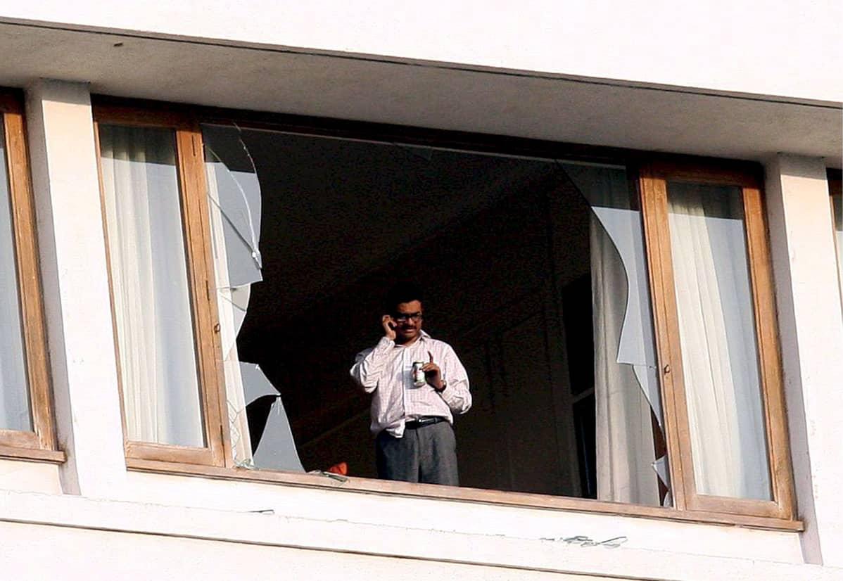 Mies puhuu puhelimeen särkyneen ikkunan takana.