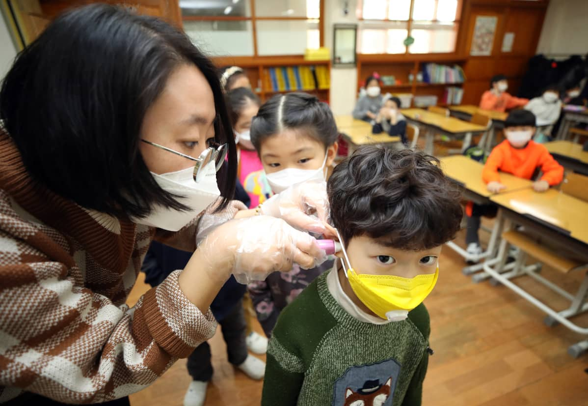 Opettaja mittaa hengityssuojaimeen pukeutuneelta oppilaalta kuumeen Soulissa Etelä-Koreassa 30. tammikuuta 2020.