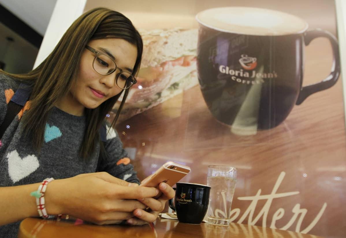 Nainen katselee puhelinta kahvilapöydässä. Pöydällä kahvikuppi ja vesilasi, seinällä samanlainen kuppi isossa julisteessa.