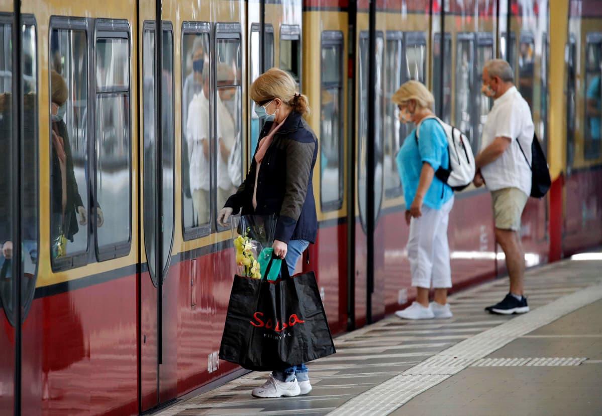 Kasvomaskeihin pukeutuneita matkustajia menossa paikallisjunaan Berliinissä. Maskit tulivat maanantaina pakolliseksi joukkoliikenteessä.