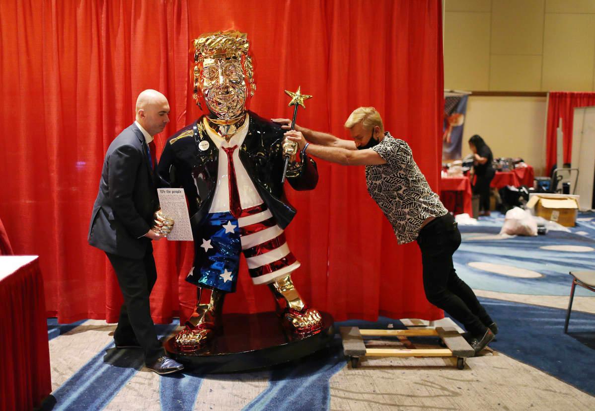Kaksi miestä roudaa kultaista Trump-patstasta.