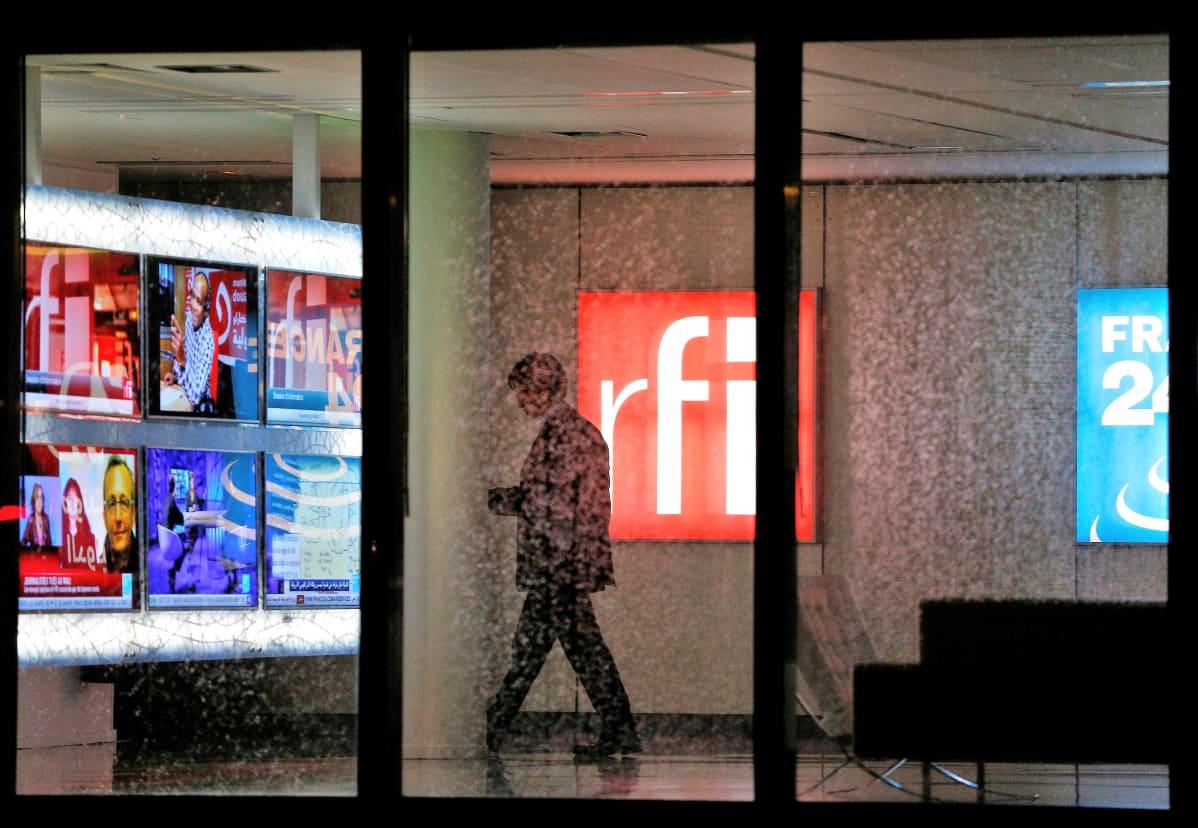 Kuva RFI:n aulasta. Mies kävelee RFI:n punavalkoisen logon ohi. Vasemmalla näkyy televisionäyttöjä, joissa on meneillään uutislähetyksiä. Oikeassa reunassa näkyy France24-uutiskanavan logo.