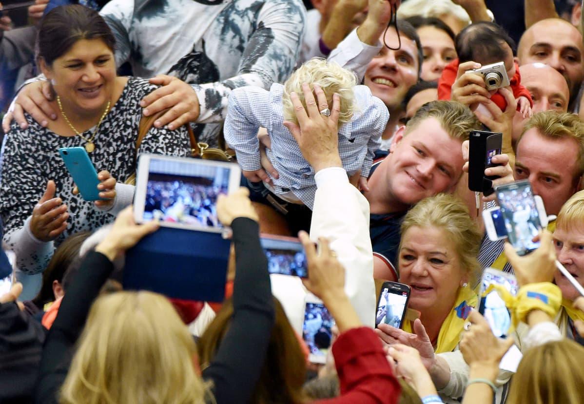 Paavi Franciscus koskettaa lapsen päätä Vatikaanissa.