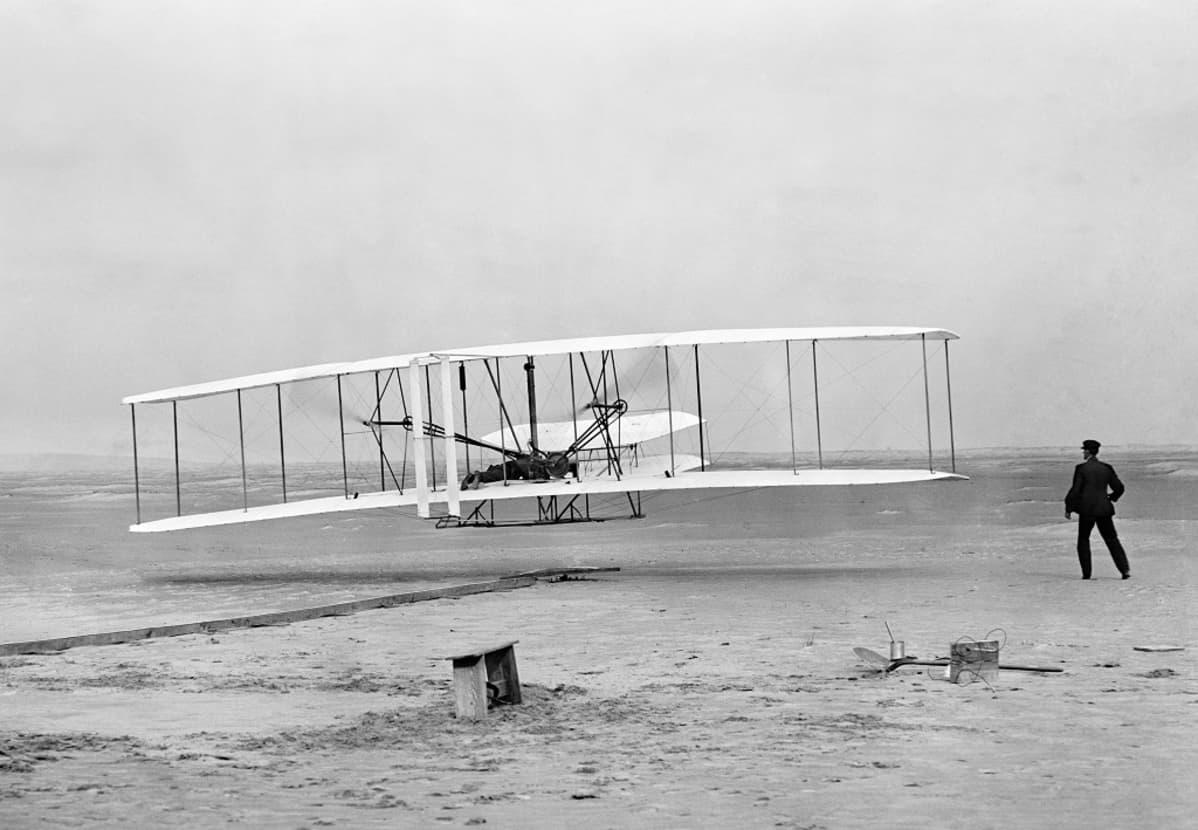 Mustavalkoinen kuva kaksitasolentokoneesta hieman maanpinnan yläpuolella ja miehestä koneen lähellä.