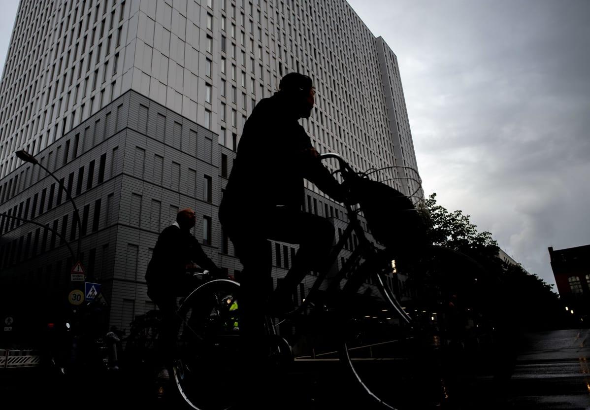 Pyöräilijä ohittaa Charitén sairaalan Berliinissä. Taivas on pilvinen. Sairaalarakennus nousee korkeana kohti taivasta.