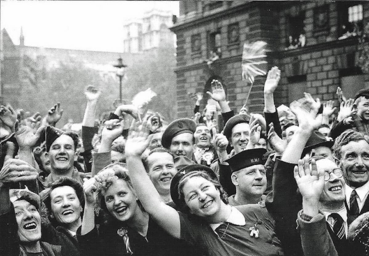Mustavalkoinen kuva iloisista ihmisistä, jotka heiluttavat käsiään ja Britannian lippua.
