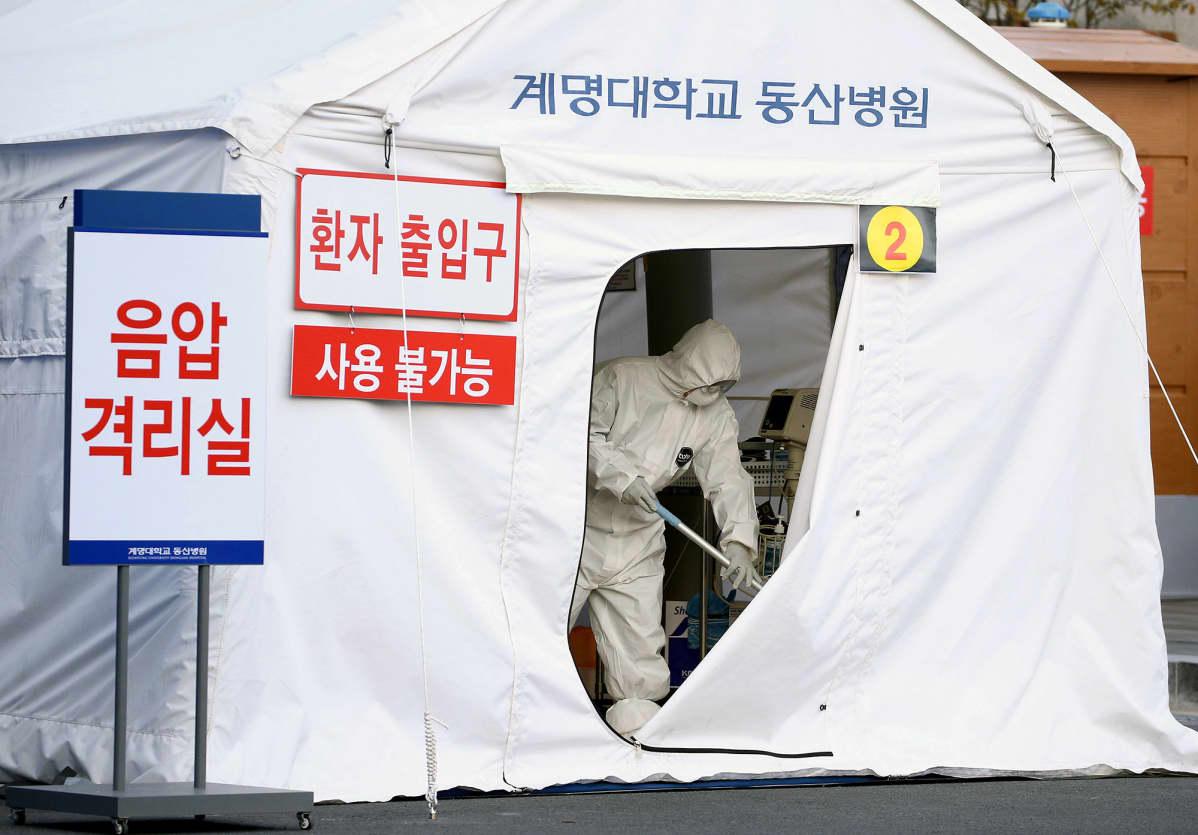 Työntekijät siivoavat karanteenitelttaa Etelä-Korean Daegussa.