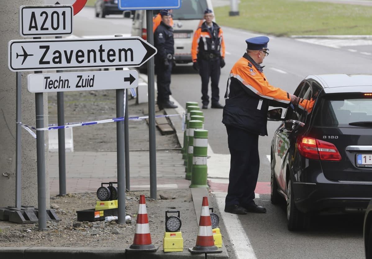 Poliisi ojentaa kätensä autoon kadulla, jonka laidalla kyltti viittaa Zaventemin lentokentälle.