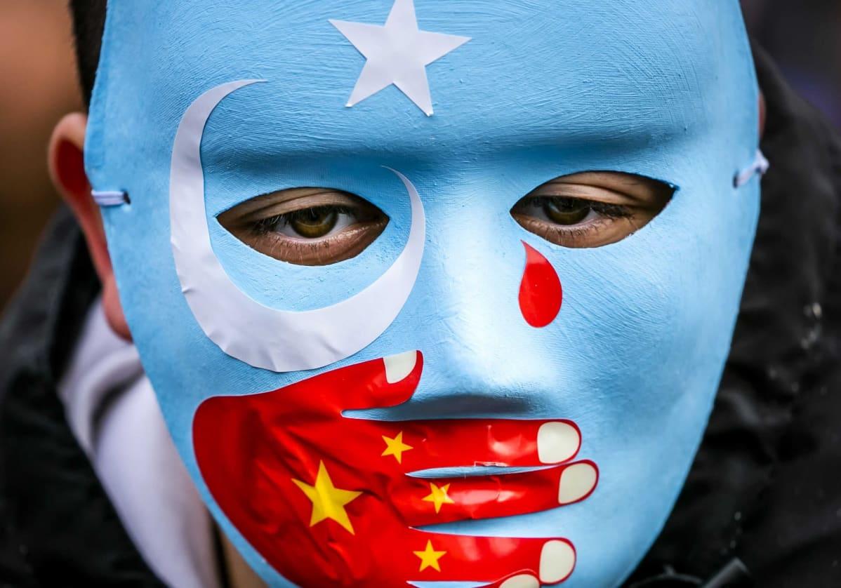 Naamari, jonka suuaukkoa peittämään on maalattu käsi Kiinan lipun väreissä.
