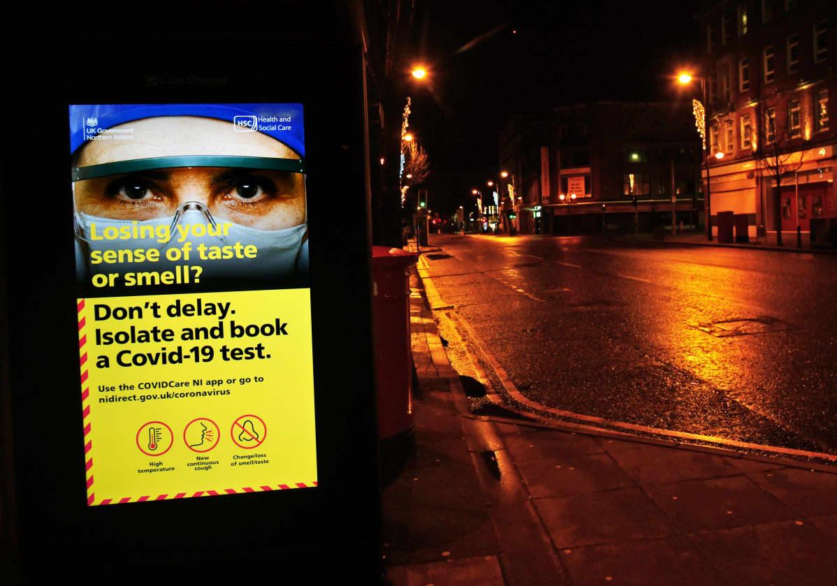 Taustalla hämärä katu, jalkakäytävällä mainostaulu, jossa kuva suojalaseilla ja maskilla peitetyistä kasvoista