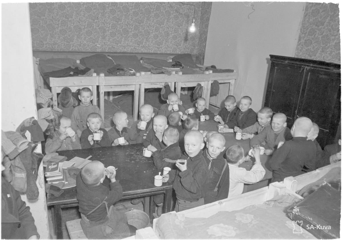 Noin kaksikymmentä poikalasta syömässä ahtaassa tilassa jossa on kerrossänkyjä.