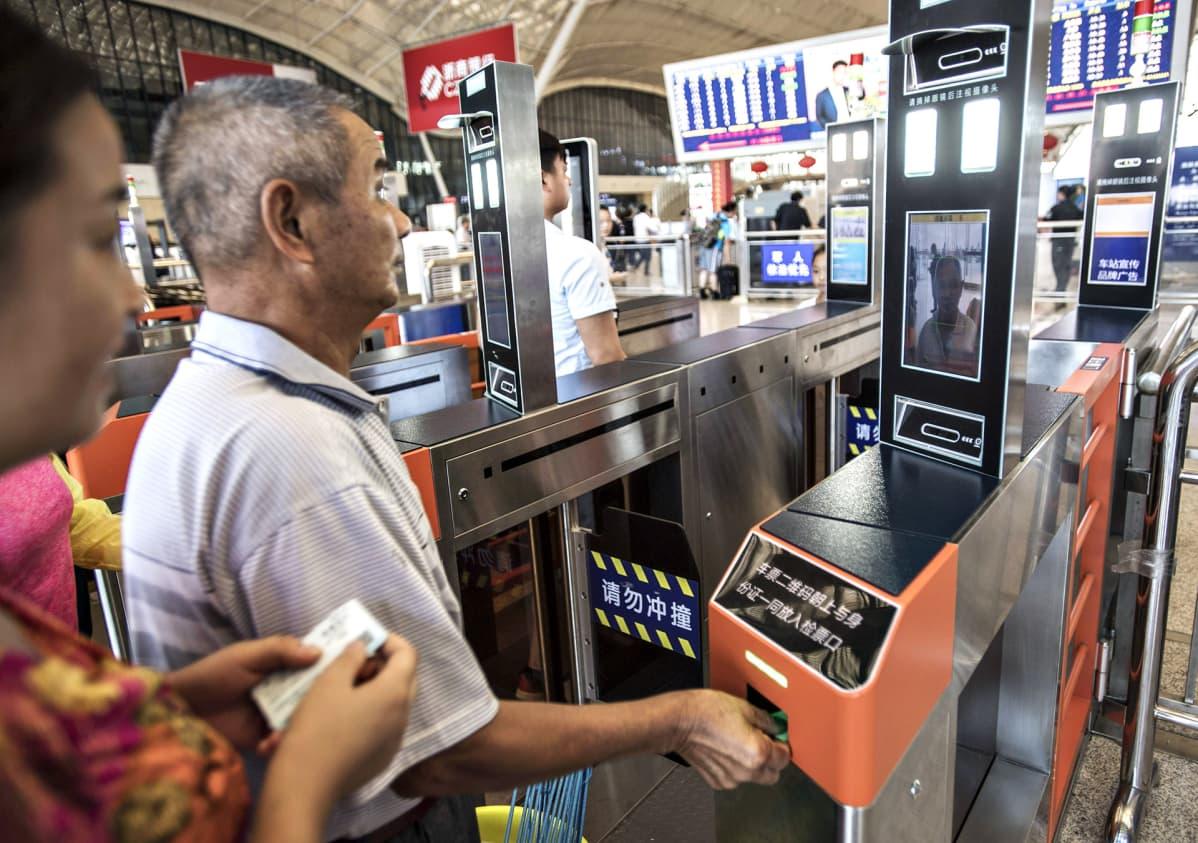 Matkustaja käyttää henkilökorttia kasvojentunnistuslaitteessa mennessään junalaitureille Wuhanin rautatieasemalla.