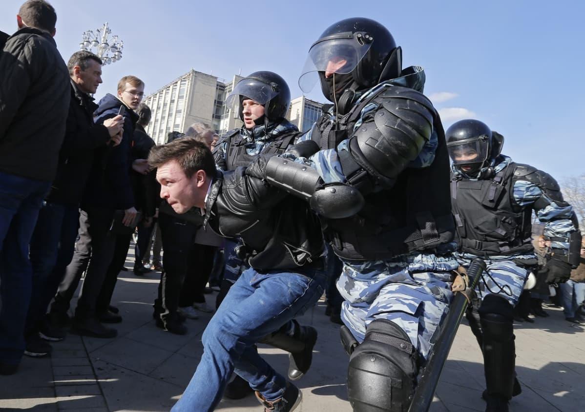 Kaksi mellakkapoliisia raahaa mielenosoittajaa, jolla on musta nahkatakki jua farkut.