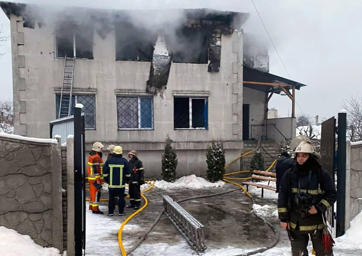 Palomiehiä savuavan talon edustalla.