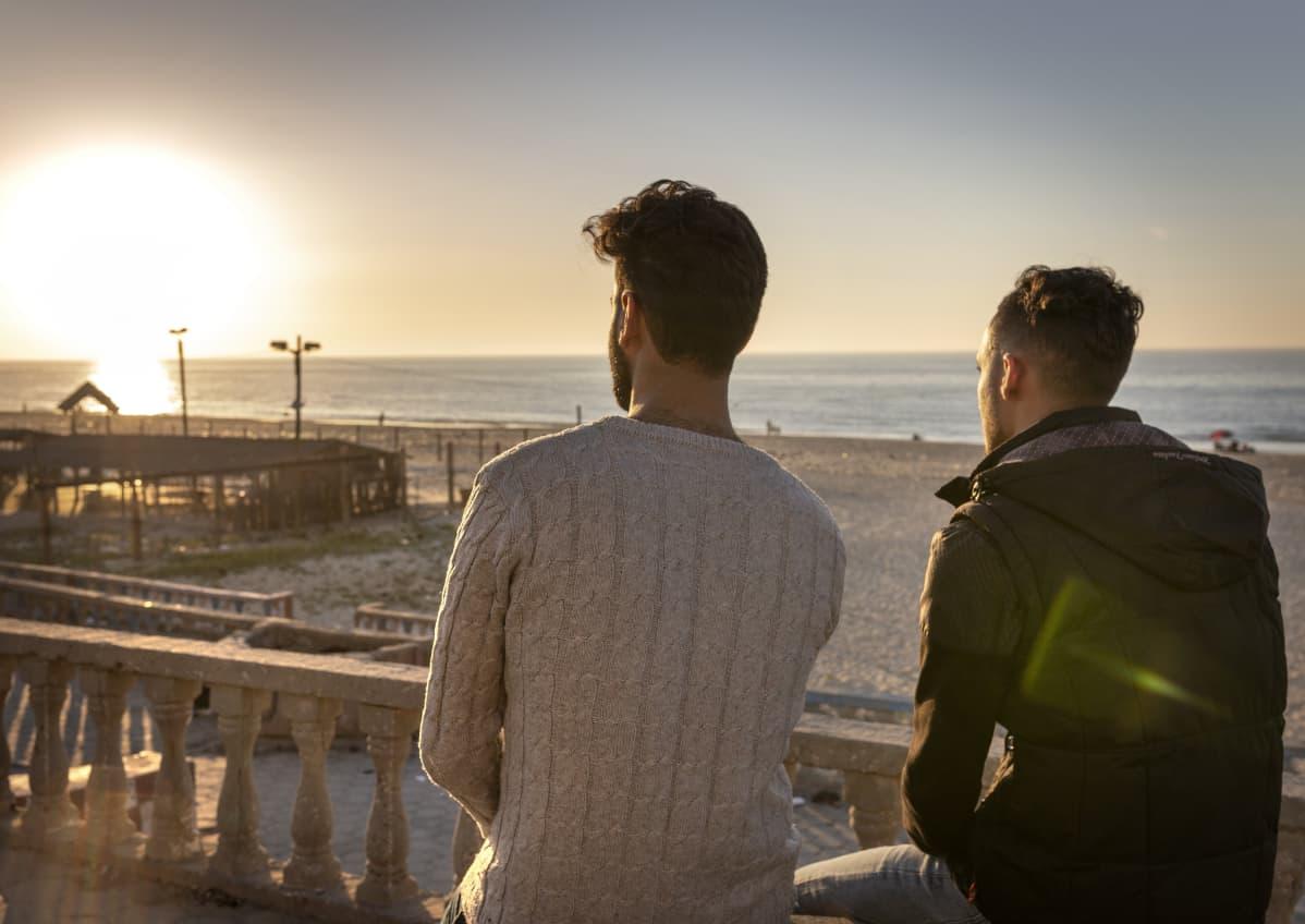 Ismail Matar ja Abdallah AlQassab istuu rannalla selkä kameraan päin.