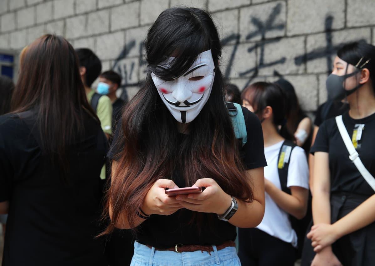 Nainen kirjottaa jotakin kännykällään Guy Fawkes maski kasvoilla