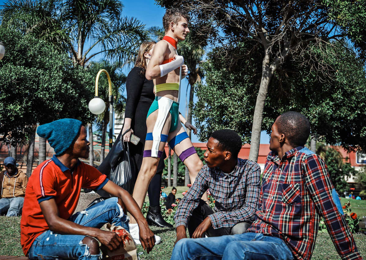 Nuoret miehet katselevat Pride-kulkueen osallistujia.
