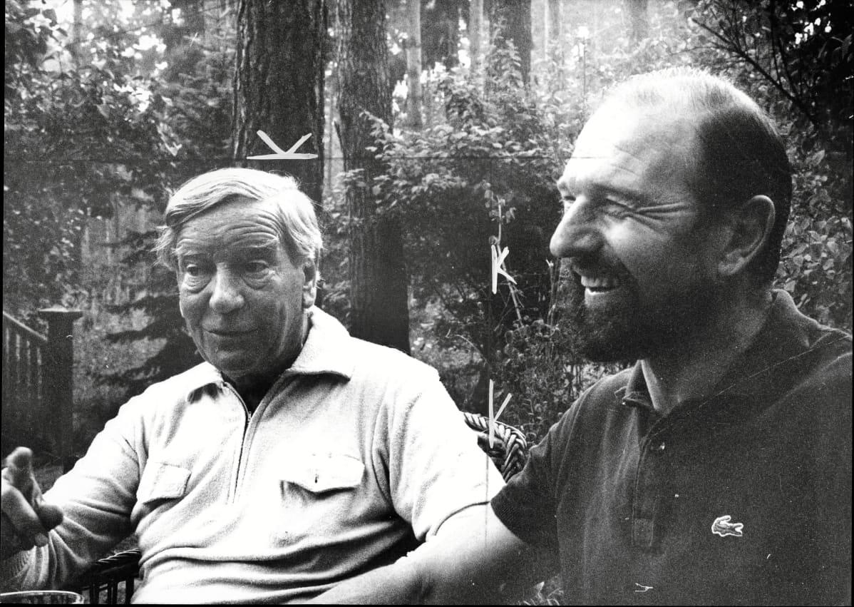 Mustavalkoisessa kuvassa Philby ja Blake istuvat puutarhassa. Philby selittää jotain ja Blake nauraa.