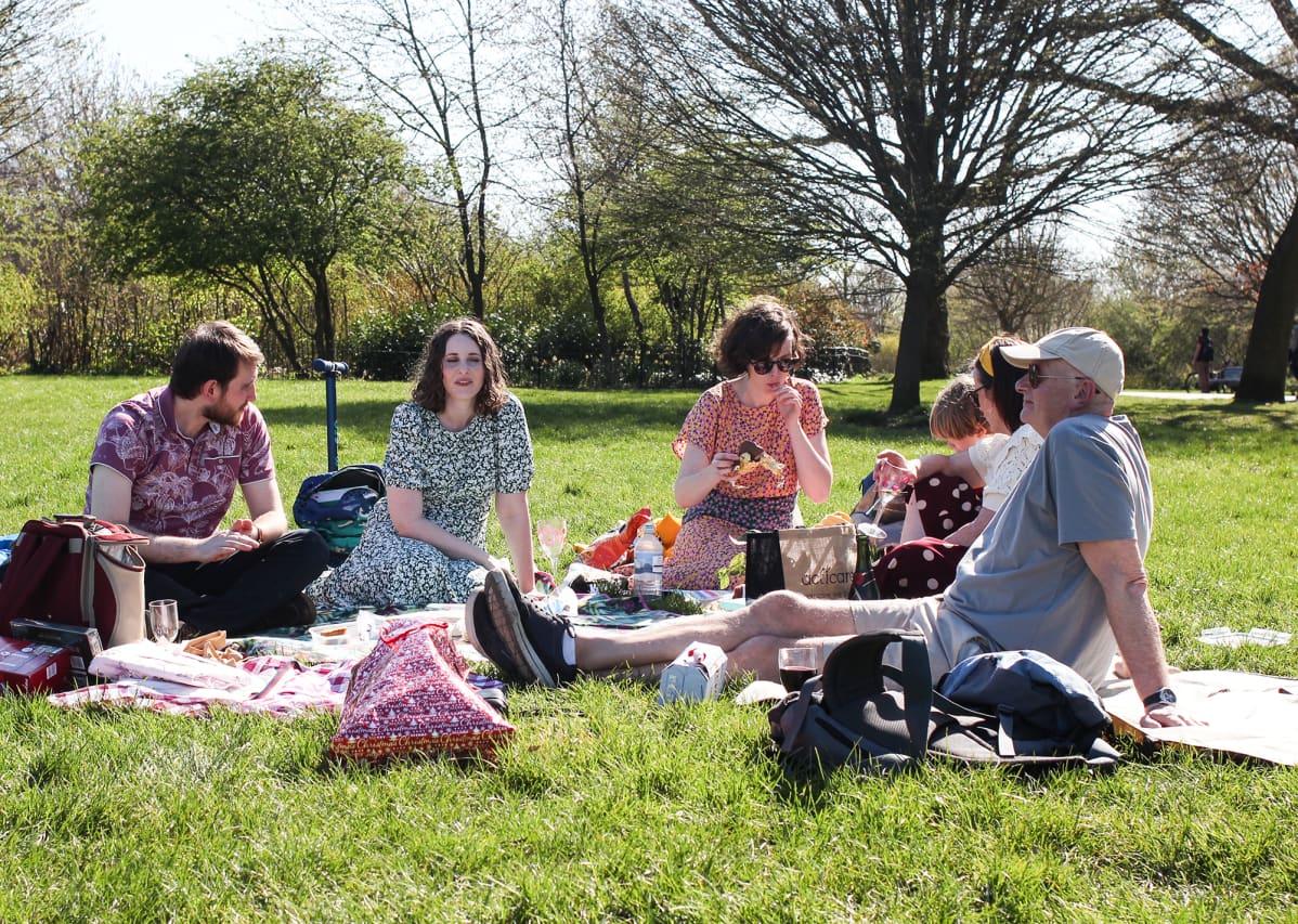 Ihmisiä istumassa eväineen nurmikolle levitetyillä alustoilla