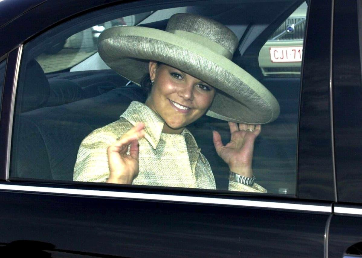 Hattupäinen Victoria vilkuttaa autosta.