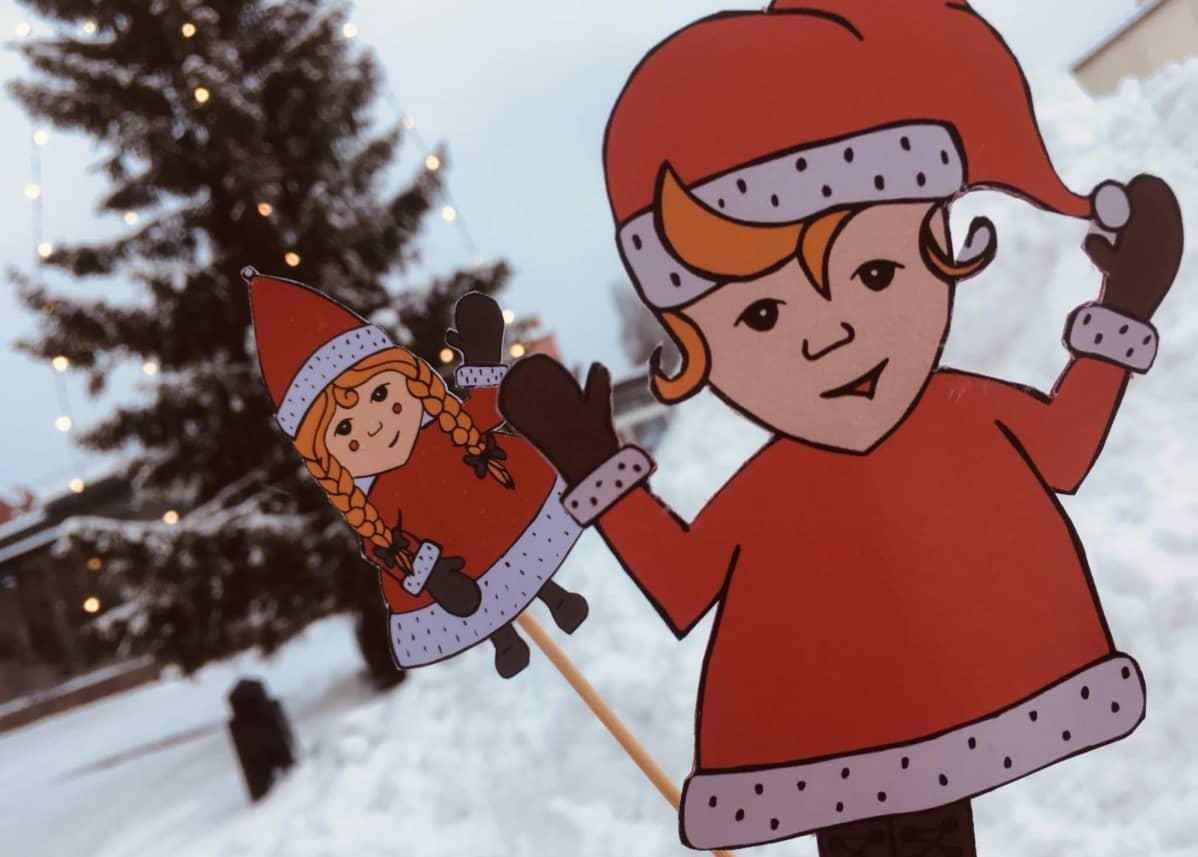Pahvisia joulutonttuja lumisella torilla.