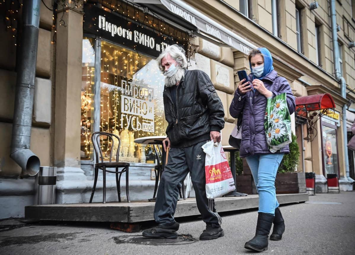 Mies ja nainen kulkevat ostoskadulla kauppakasseineen  ja maskit kasvoillaan