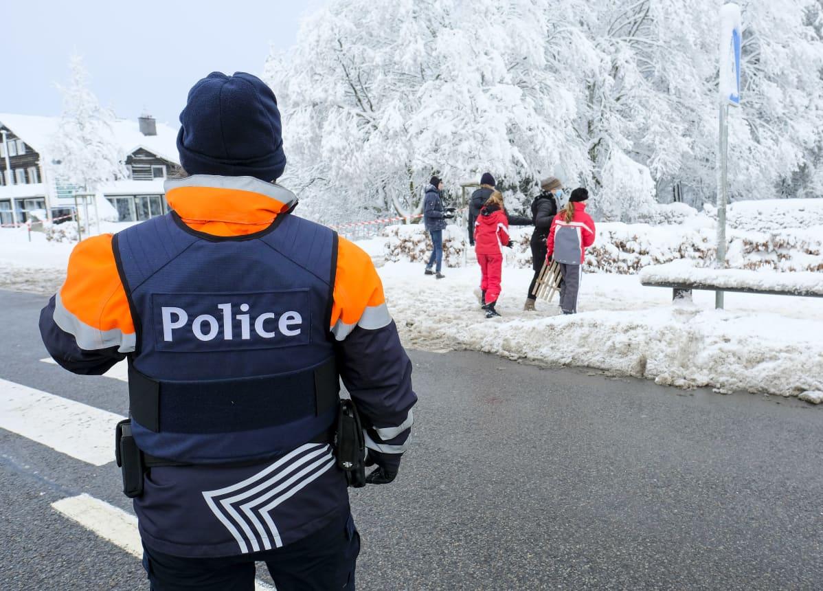Poliisi seisoo selin kameraan, taustalla joukko ihmisiä mäenlaskuvarusteiden kanssa lumisessa maisemassa