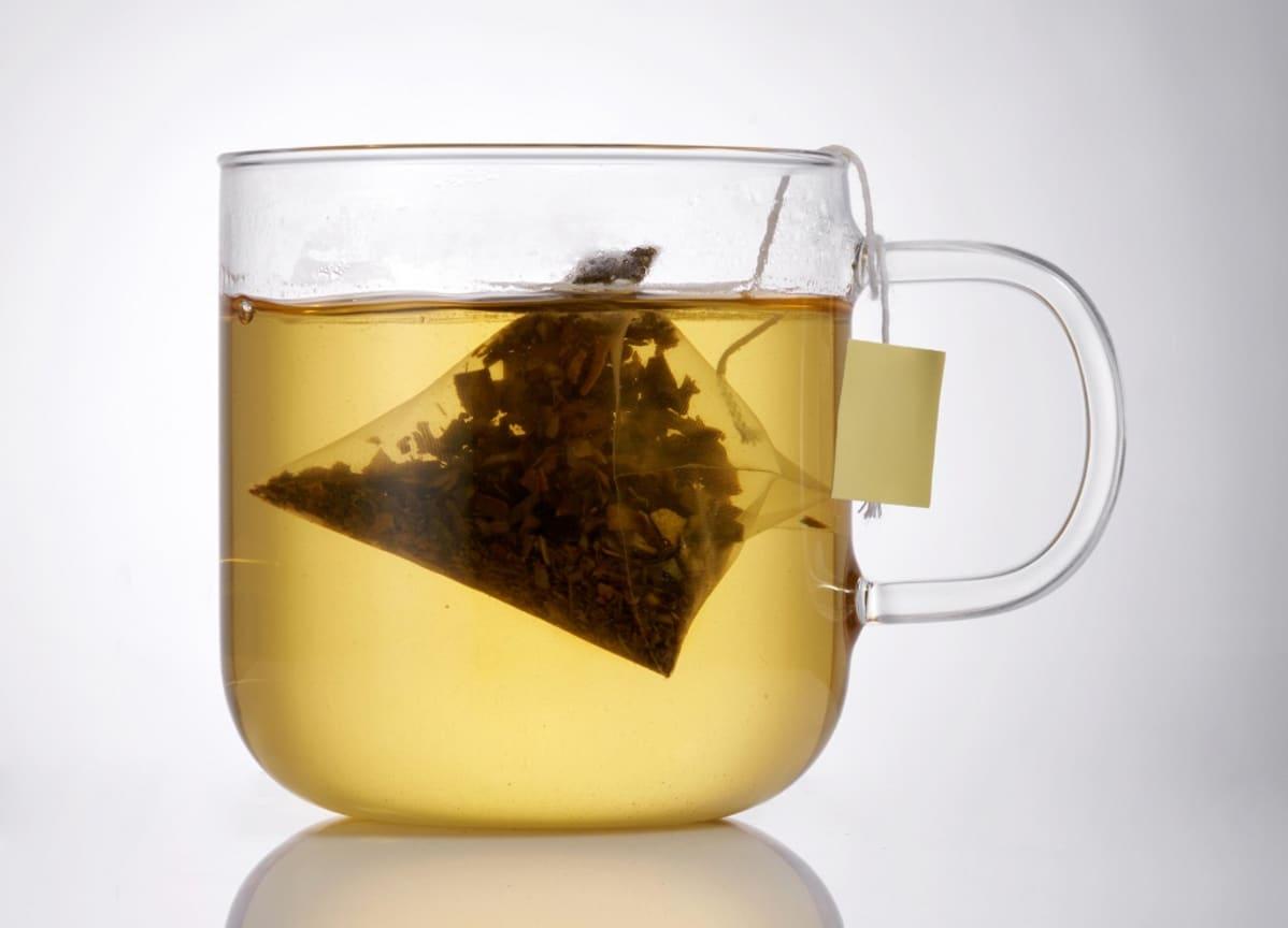 Pyramidin muotoinen teepussi lasisessa teekupissa.
