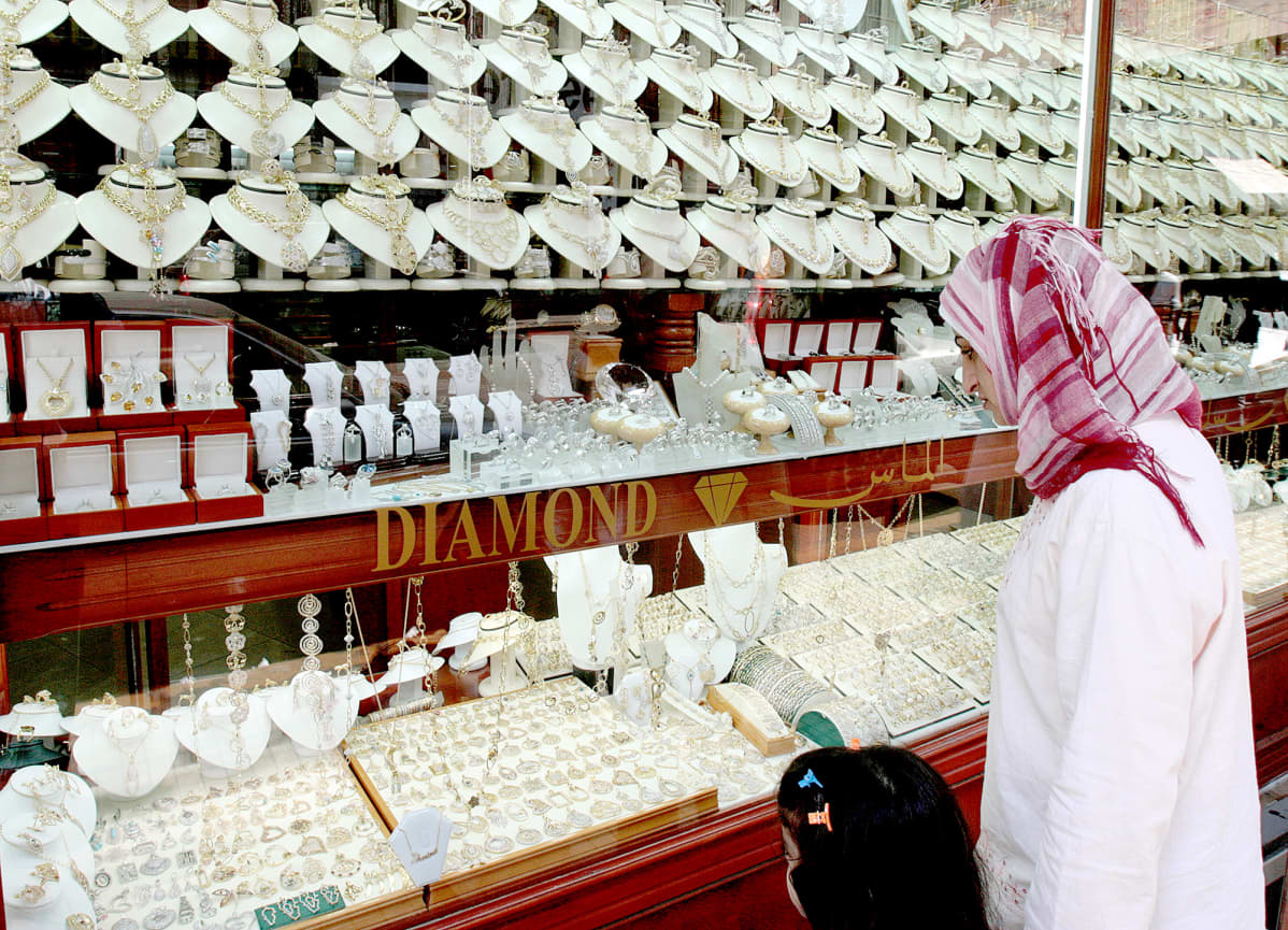 Nainen katselee koruja korukaupan näyteikkunassa Beirutissa.