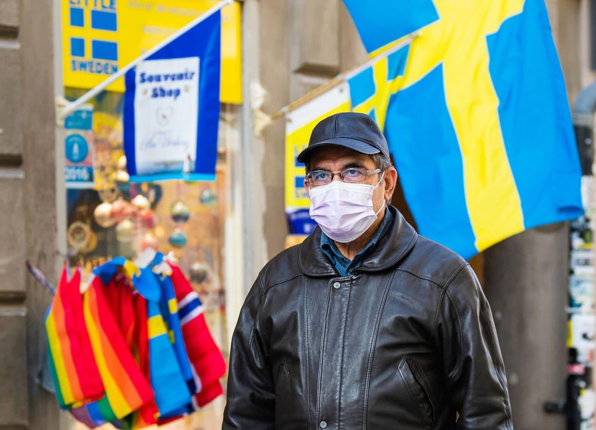 Hengityssuojaan pukeutunut mies kävelee kadulla Tukholmassa.