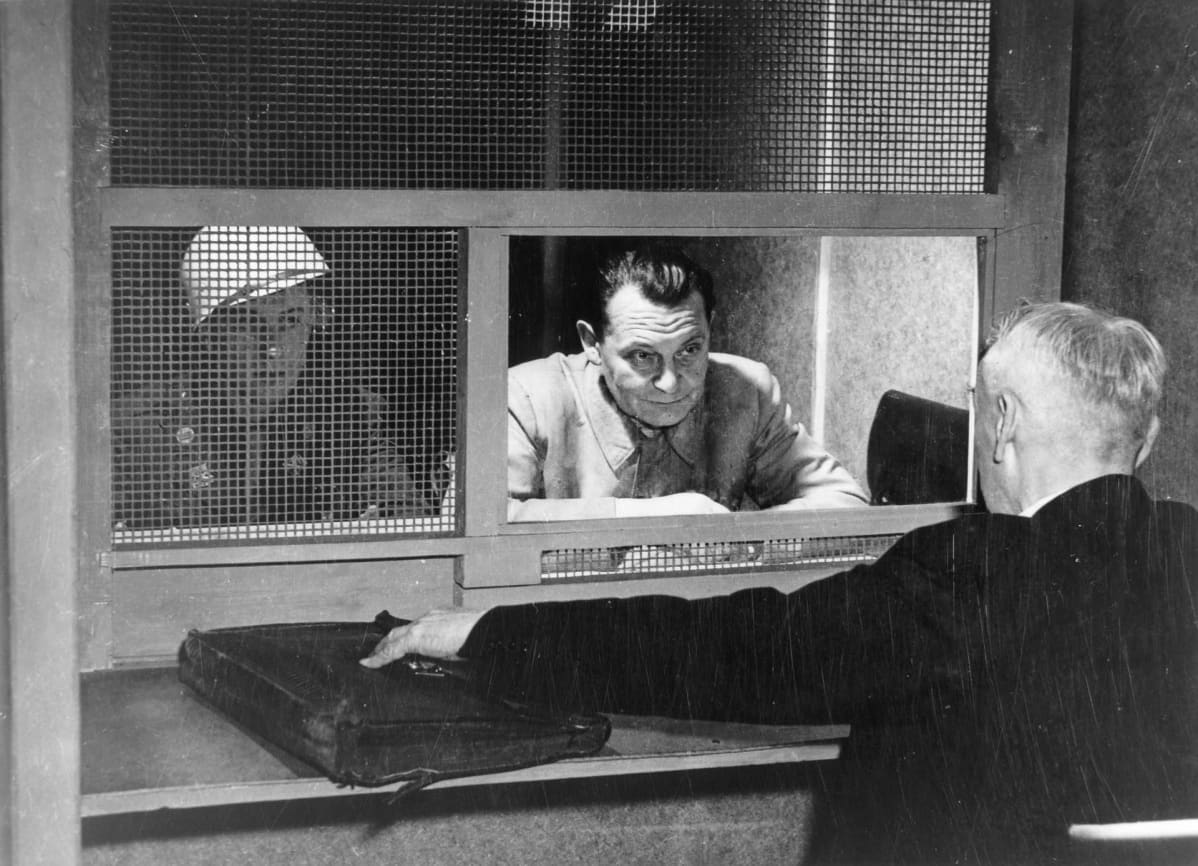 Hermann Göring keskustelee luukun läpi asianajajansa kanssa. Sotilas vartioi.