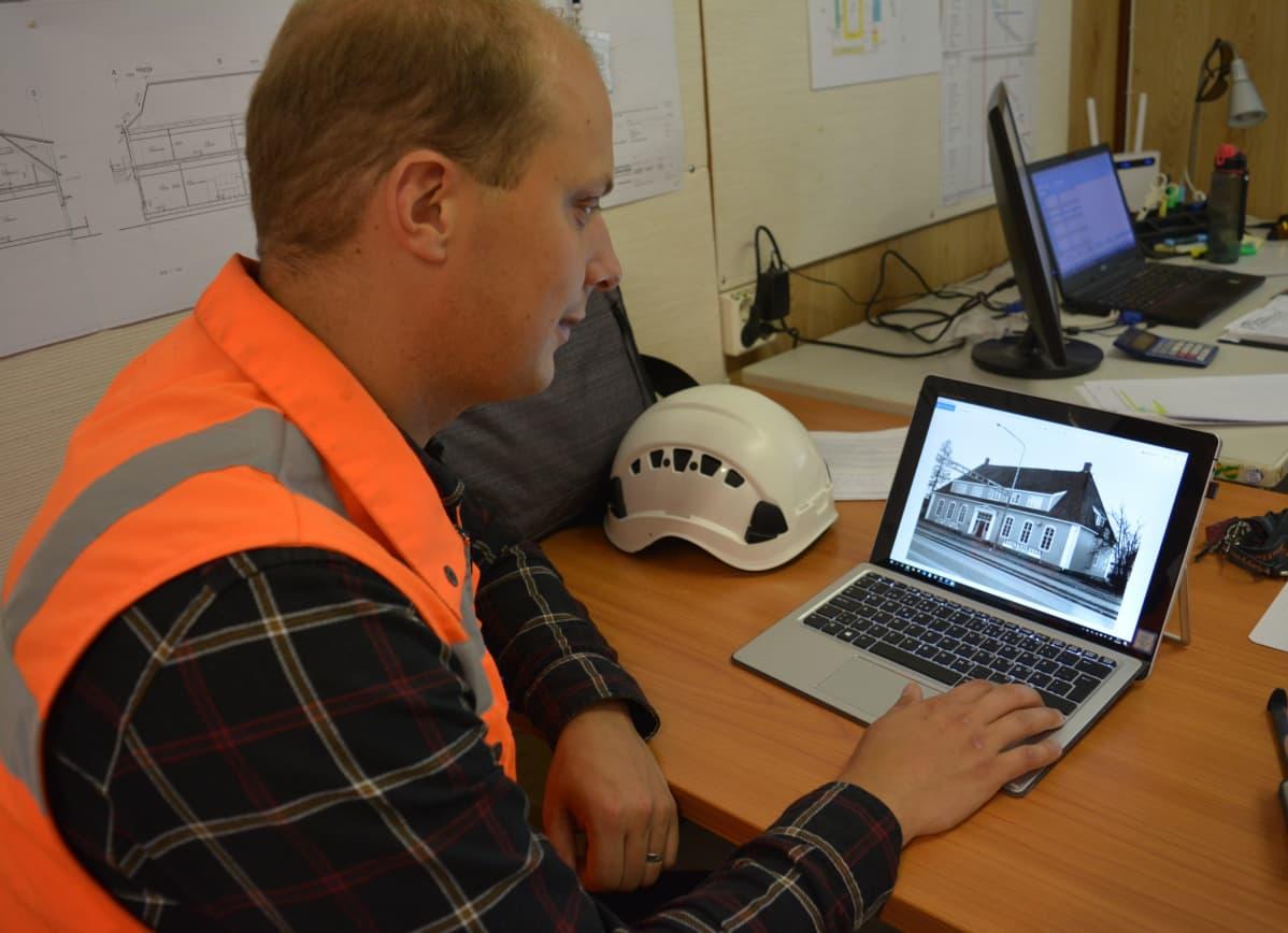 Työpäällikkö Laurimatti Laine Rakennus K. Karhulta vertaa Vanhan Kauppalantalon kuvia uusiin havainnekuviin.