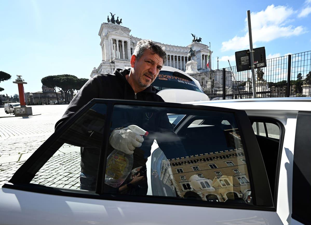 Taksikuski puhdistaa autoaan Roomassa.