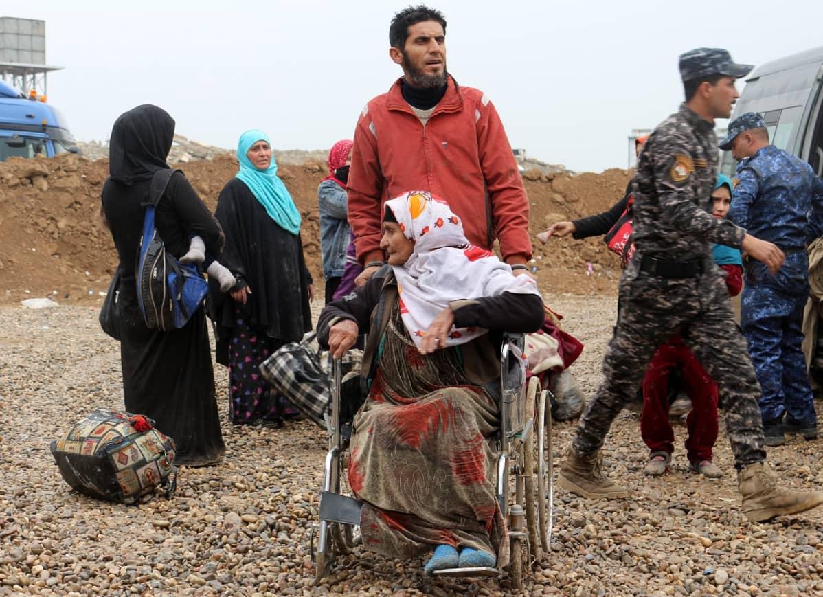 Mies työntää rullatuolissa olevaa vanhempaa naista, taustalla naisia ja sotilaita.