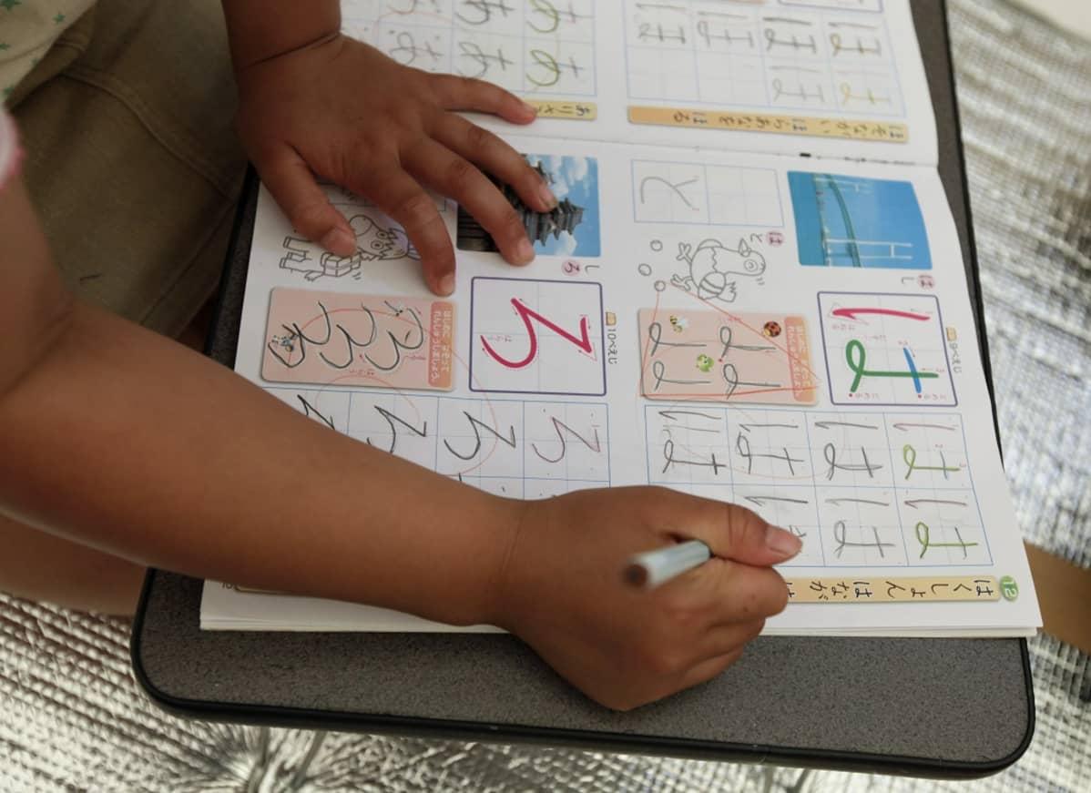 Koulukirja, johon pieni tyttö piirtää japanilaisia kirjainmerkkejä kuvien viereen.