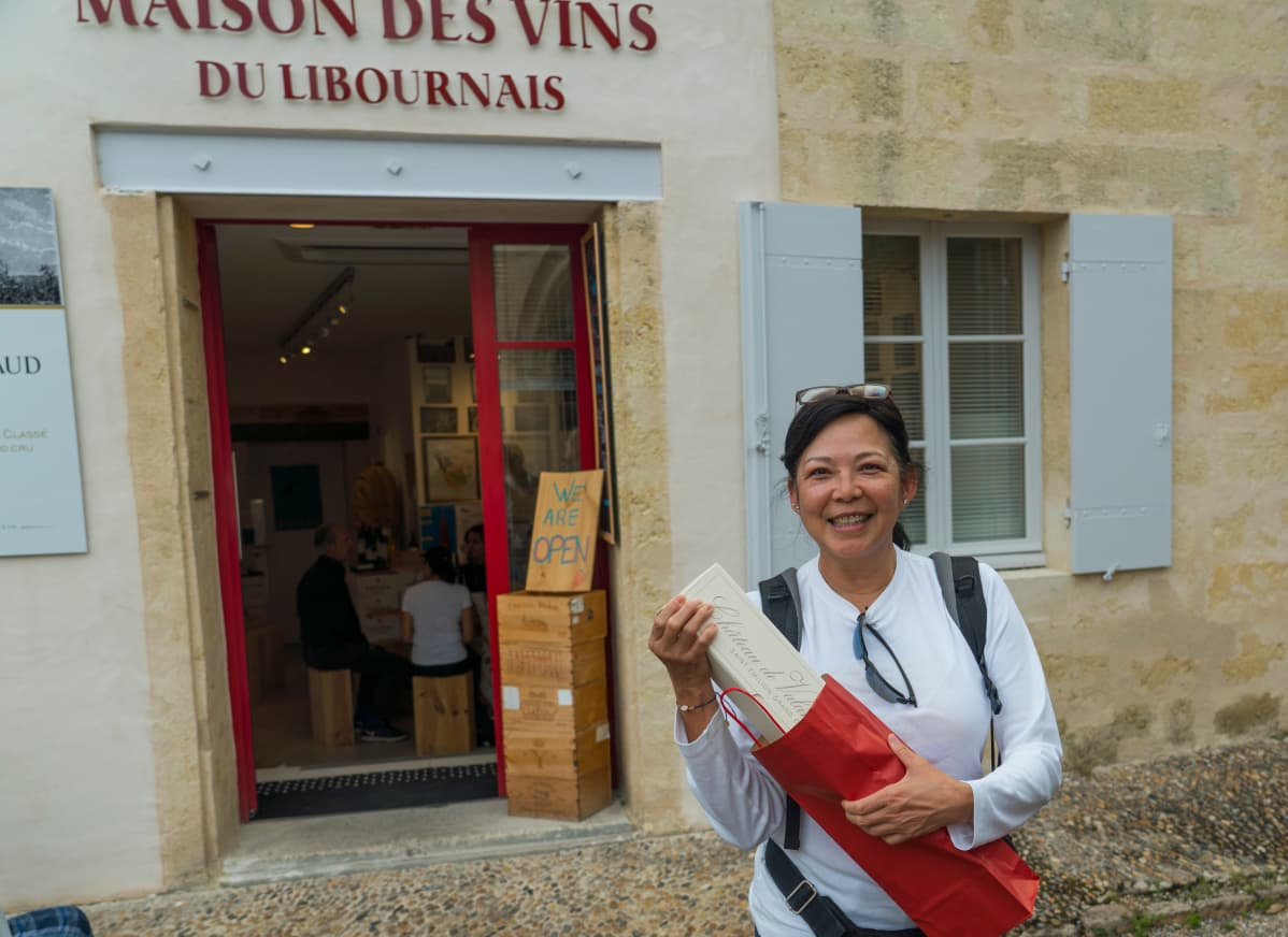 Nainen viinikaupan edustalla.