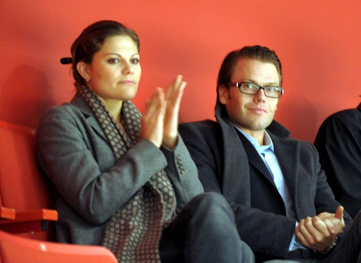 Pari istuu vierekkäin katsomossa.