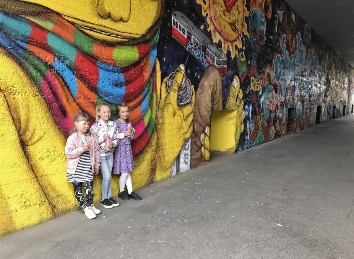 Kolme lasta graffitiseinän edessä.