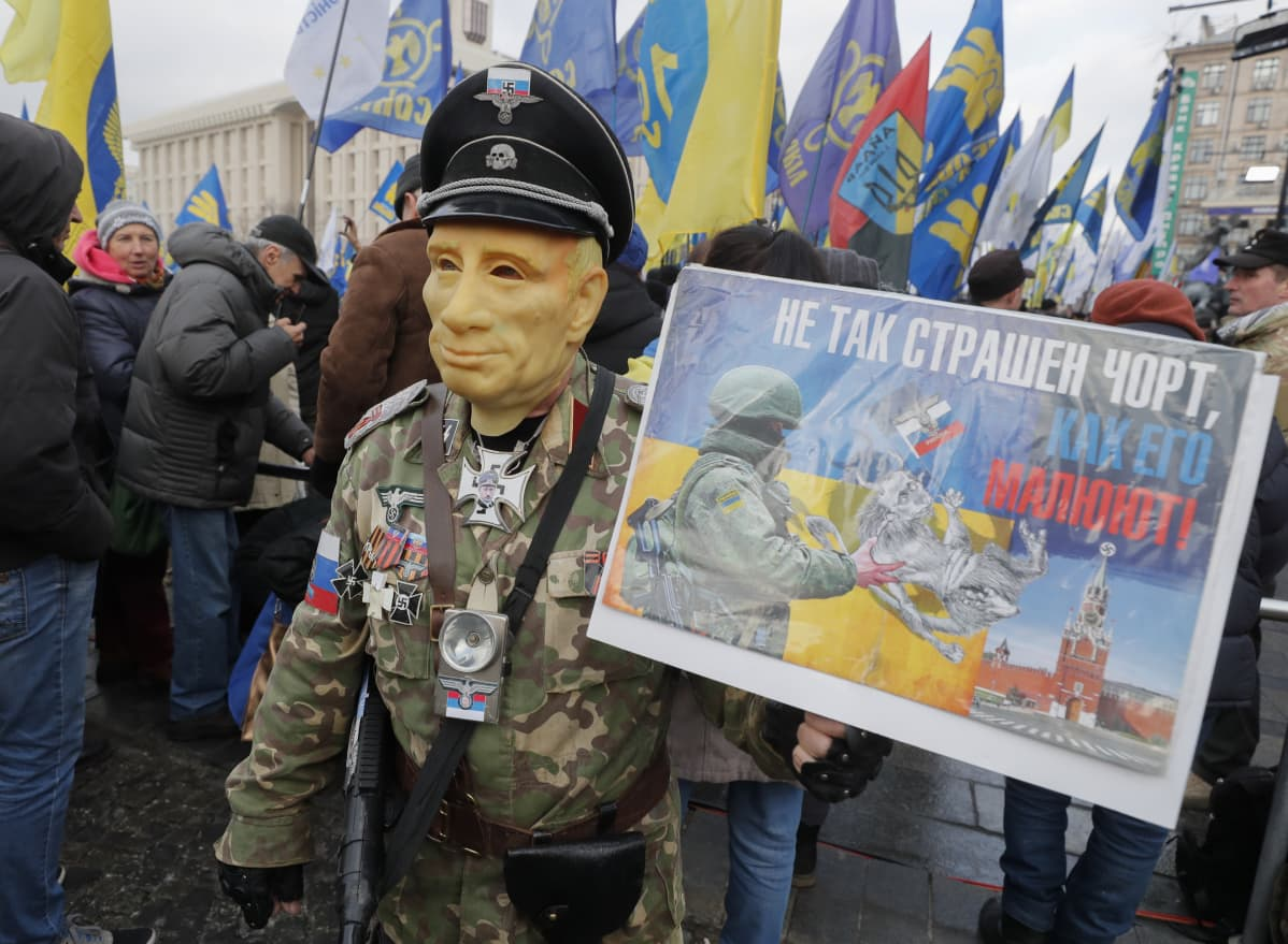 Putiniksi naamioitunut asepukuun pukeutunut mielenosoittaja pitää kädessään Putinin vastaista julistetta