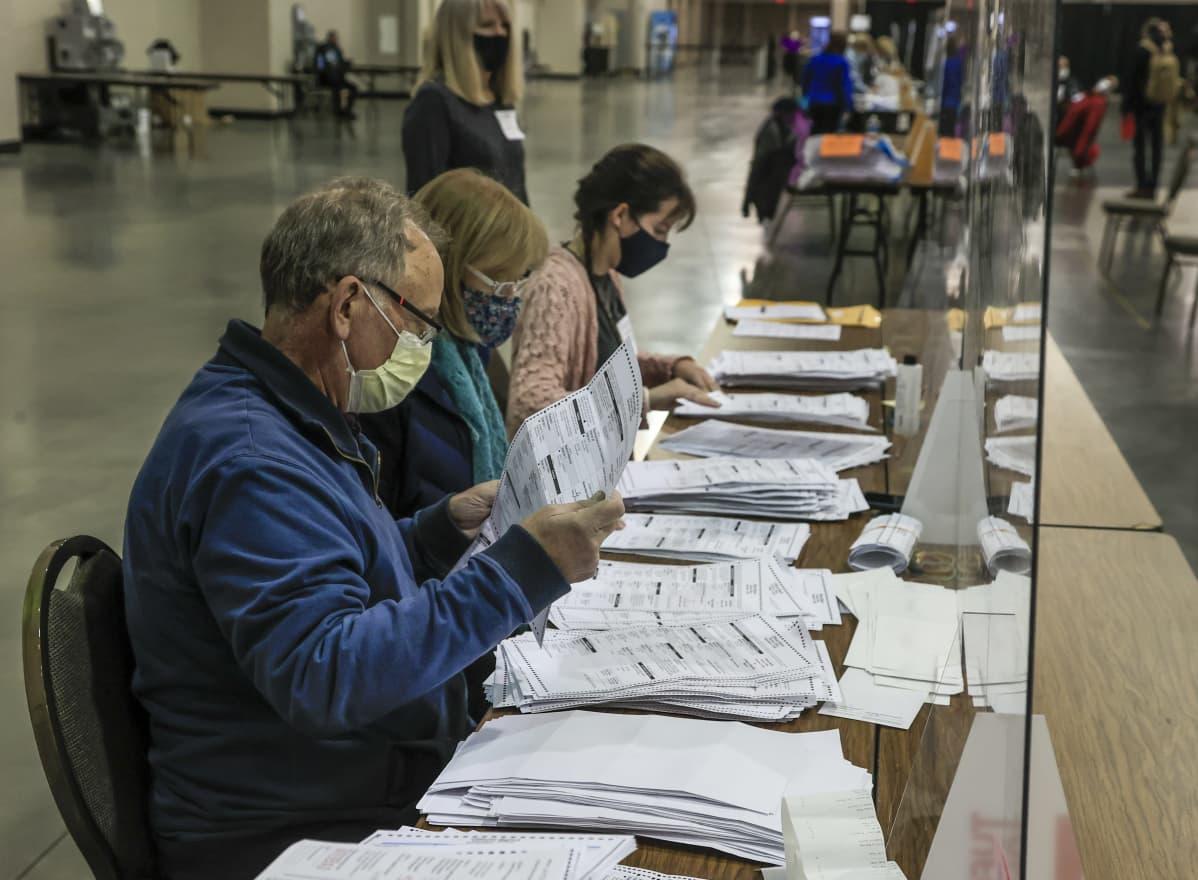 Kolme ääntelaskijaa kasvomaskeissa käsittelee vaalilippuja Wisconsinissa.